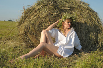 portrait of beautiful blonde country girl sittitng on yellow hay with bunch of flowers