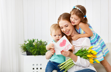 Happy mother's day! Children congratulates moms and gives her a postcard and flowers