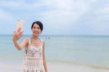 Woman taking photo by mobile phone in sand beach