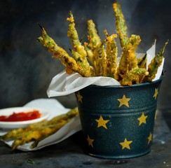 Batter Fried green Beans served in a rustic metal bucket on moody background, selective focus
