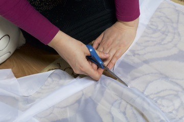 The woman cuts the fabric with scissors for sewing curtains on the window. The fabric lies on the floor. View from above.