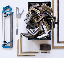 Overhead view of picture frames and corners with work tools on table in workshop