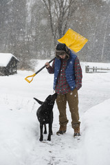 Man carrying shovel while standing with dog on snow covered field