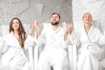 Three friends in bathrobes meditating in the salt room
