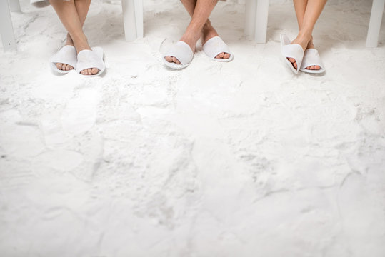 Three friends relaxing in the salt room. Defocused legs with copy space