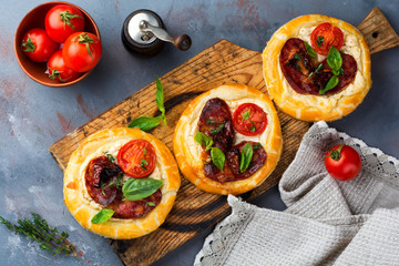 Mini tarts with dried meat, tomatoes, ricotta, thyme, basil and olives on a gray concrete background. Rustic style. Selective focus. Top view.