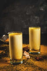 Traditional Indian drink turmeric milk is golden milk with cinnamon, cloves, pepper and turmeric. On a concrete table, with spices on the background. In glasses, toned copy space