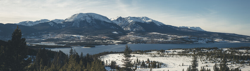 Panoramic view of river against mountains during winter