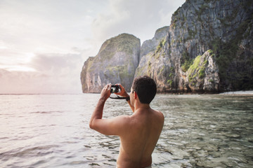 Rear view of shirtless man photographing while standing at beach