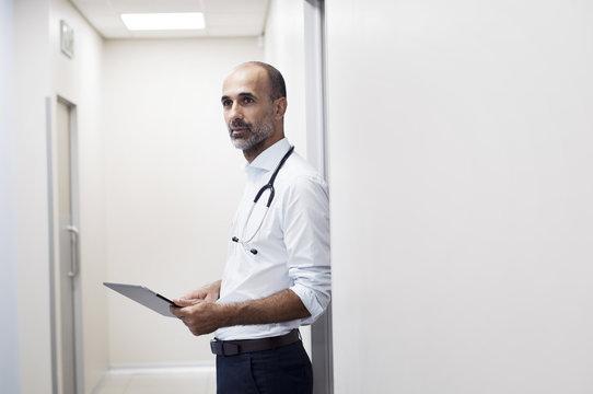 Doctor with tablet computer looking away while standing by door in corridor