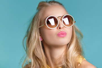 portrait of beautiful blond woman in sunglasses and yellow shirt on  blue Carefree summer.