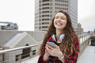 Cheerful woman using smart phone while standing at terrace cafe