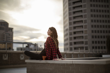 Young woman sitting on seat at terrace against buildings