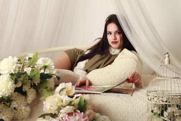 Beautiful girl lying on the bed with sheer curtains and looking photo album with flowers
