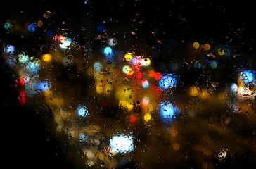 Colorful, abstract bokeh blur bubble style effect of a city lights and traffic at night on a window with rainy drops, made with Zeiss lens