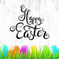 Happy Easter handwritten calligraphy lettering with colorful eggs and grass on wood background. Vector illustration.