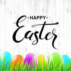 Happy Easter handwritten calligraphy lettering with colorful eggs and grass on wood texture background. Vector illustration.