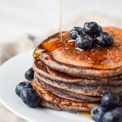 syrup is poured on top of lemon poppy seed pancakes with blueberries