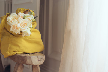 sac en lin avec des roses posées sur un banc