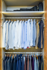 Men's wardrobe with jackets and shirts on hangers
