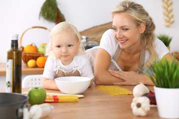 Happy family in the kitchen. Mother and child daughter  cooking tasty breakfast