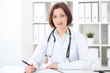 Young brunette female doctor sitting at the table and working at hospital office.  Health care, insurance and help concept. Physician ready to examine patient