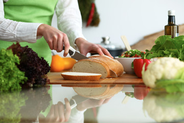 Closeup of human hands slicing bread in kitchen on the glassr table with reflection. Healthy meal and vegetarian concept