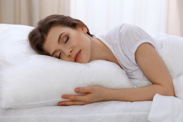Beautiful young woman sleeping while lying in bed comfortably and blissfully. Early morning, you wake up for work or the day off concept