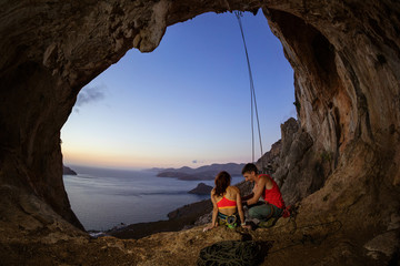 Couple of rock climbers resting in cave