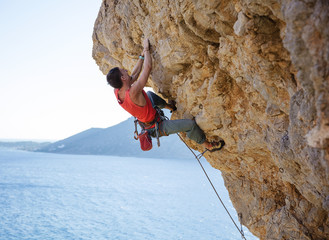 Young man struggling to climb overhanging cliff