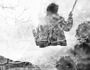 Monochrome double exposure of kid on swing and autumn branches
