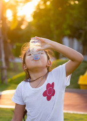 Asian little Girl Drink Water with Plastic bottle in Park or Playground in Summmer dueling Dueling Sunset