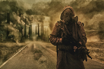 Post-apocalyptic air pollution. Survivor in tatters and gas mask on the background of pipes on abandoned road. Nature protection concept
