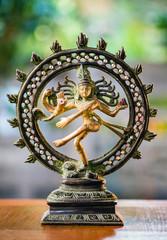 Shiva Nataraja statue on defocus/selective focus background on wooden table. India/Hindu god.