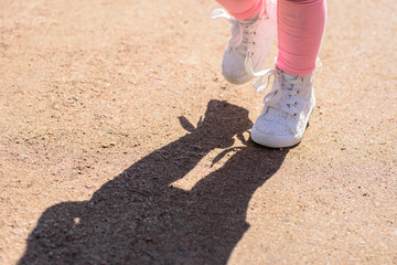 closeup of little girl's feet wearing white lace gym shoes walking on trail with shadow