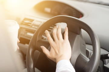 Human hand on steering and honking
