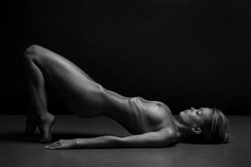 Athletic Naked woman body on black background. Fine art photo of female body.