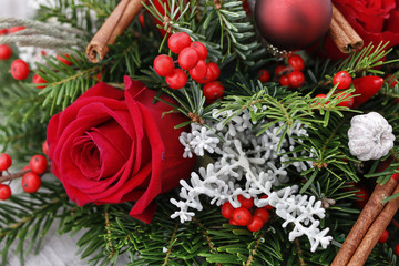Christmas decoration with red roses, fir, brunia and cinnamon sticks.