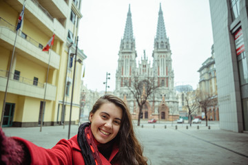 young pretty woman take selfie in front of gothic church