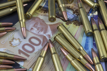Pile of bullets and Canadian money