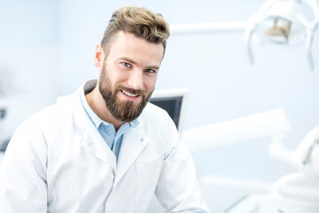 Portrait of handsome dentist in uniform at the dental office