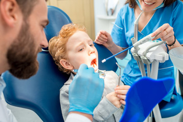 Young scared boy during the dental procedure at the dental office