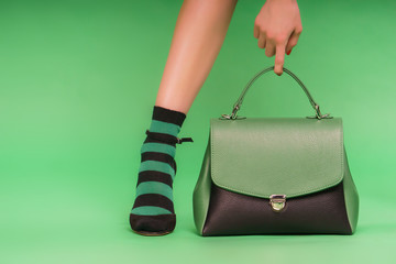 Two-colored photo: green and black handbag and woman's hand holding it on a green background.