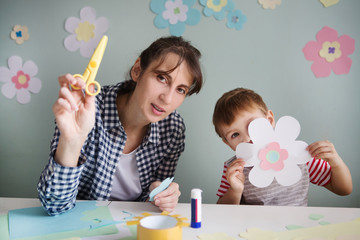 Child boy with mother have a fun cutting out scissors paper in the home. Preparation of a decor for Easter.  children's creativity.