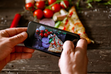 man using smartphone to take picture of slice of pizza.