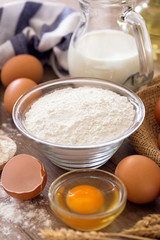 Bowl of wheat flour with eggs on the wooden.