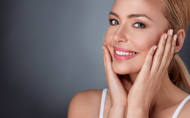 Smiling woman enjoying in her healthy skin