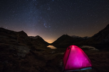 Camping under starry sky and Milky Way arc at high altitude on the italian french Alps. Glowing tent in the foreground. Adventure into the wild.