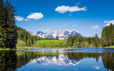 Photo sur Toile Reflexion Snowy mountain range is reflected in a small lake near Kitzbuehel, Tyrol, Austria