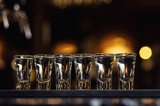 Alcoholic shots of tequila or strong drink in small glasses,Barman at work,Barman pouring hard spirit into glasses in detail, with lime garnish ready to be served,concept about service and beverages
